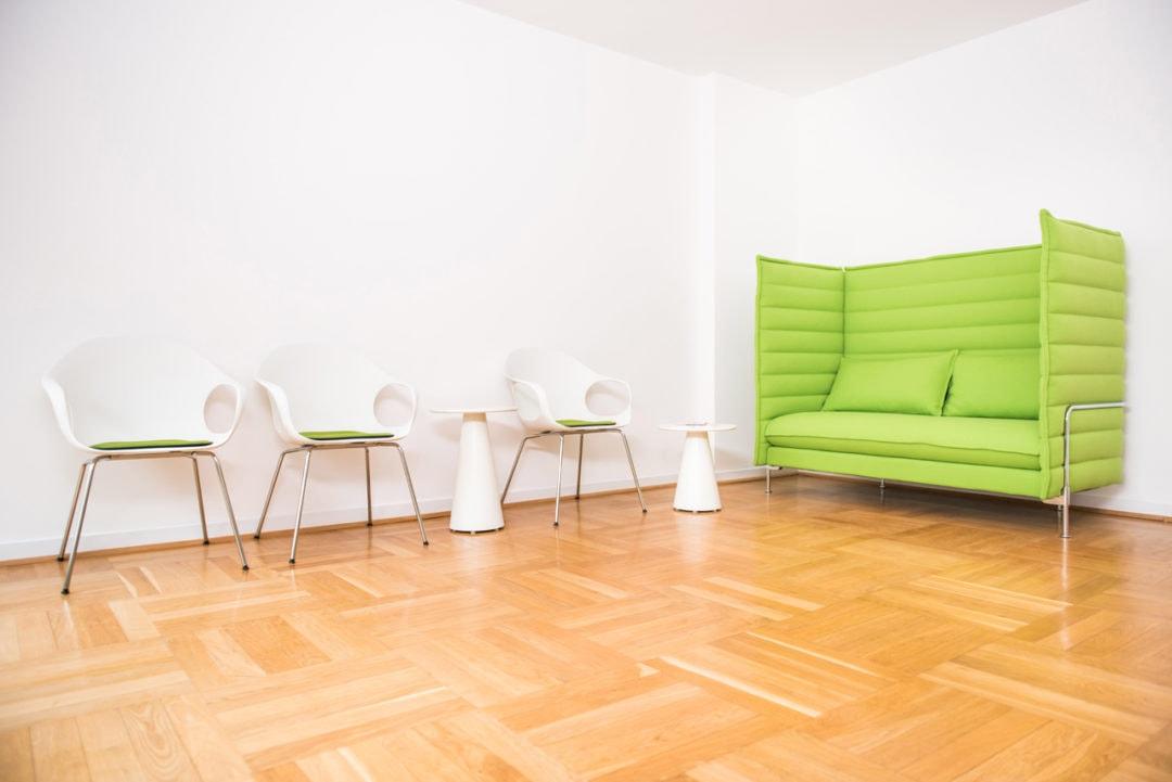 Wartebereich mit grüner Couch und weißen Stühlen in der Praxis Sentruper Höhe