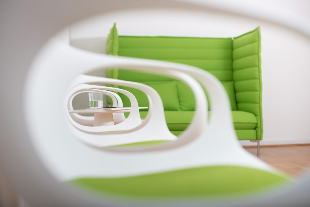 Wartezimmer mit Blick durch weiße Stuhllehne auf grüne Couch und Wasserglas auf einem Tisch