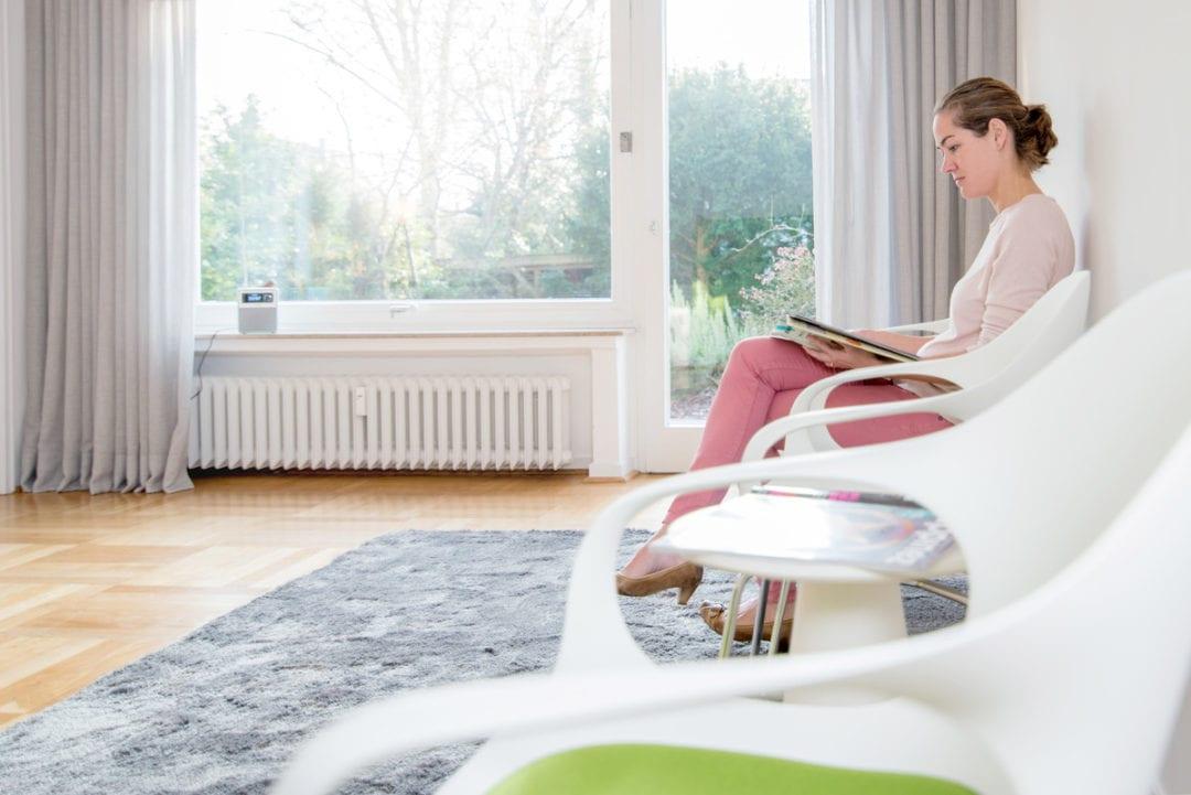Patientin sitzt in einem Stuhl im Wartezimmer und liest eine Zeitschrift