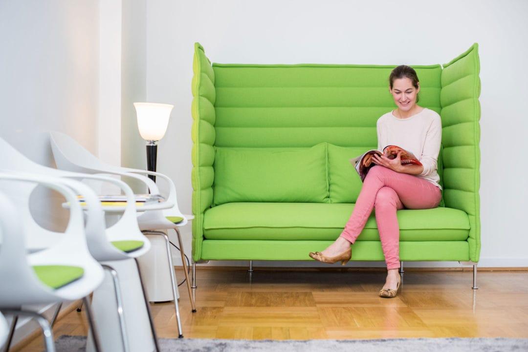 Patientin sitzt auf grüner Couch im Wartezimmer und liest eine Zeitschrift